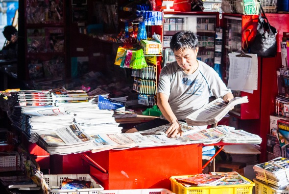 Newspaper Man, Star Ferry Pier, Kowloon, Hong Kong, China, Copyright Chris Gregory 2012